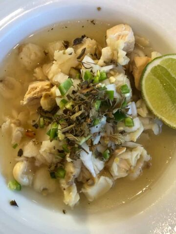 chicken pozole in a white bowl with oregano, onion, and a lime wedge