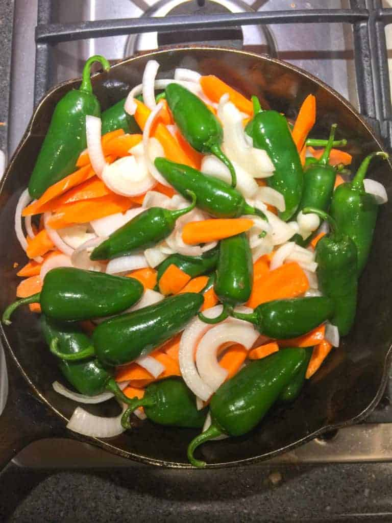 Heat olive oil in a large skillet. Add the jalapeños, carrots, and onions. Saute over medium heat for 10 minutes. Lower heat, simmer for 10 minutes.