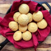 golden brown cornbread muffins in a red linen lined cast iron skillet on a wood background