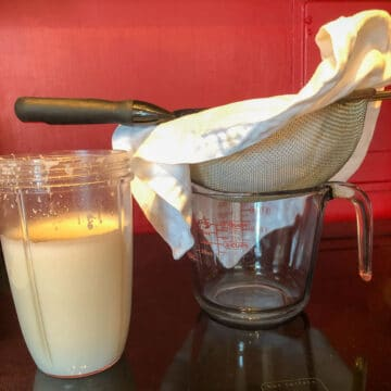 homemade coconut milk in a blender sitting next to a napkin lined strainer