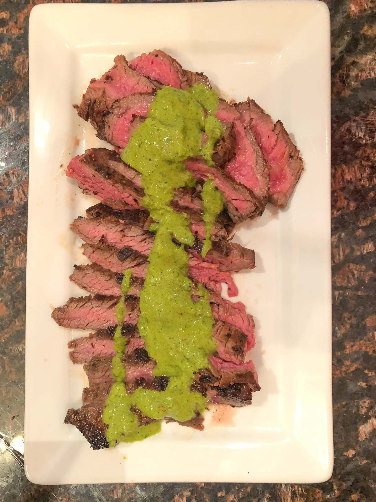 sliced medium rare flank steak topped with chimichurri sauce